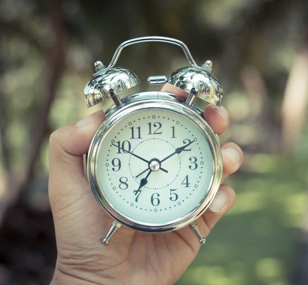 Restro classic wekker in een hand. de tijd loopt. Premium Foto