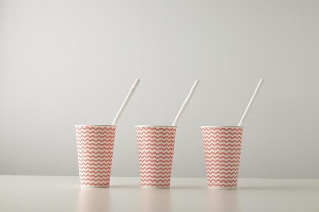 Retail set van drie papieren bekers versierd met een rood lijnpatroon en met wit rietje erin geïsoleerd op een witte tafel Gratis Foto