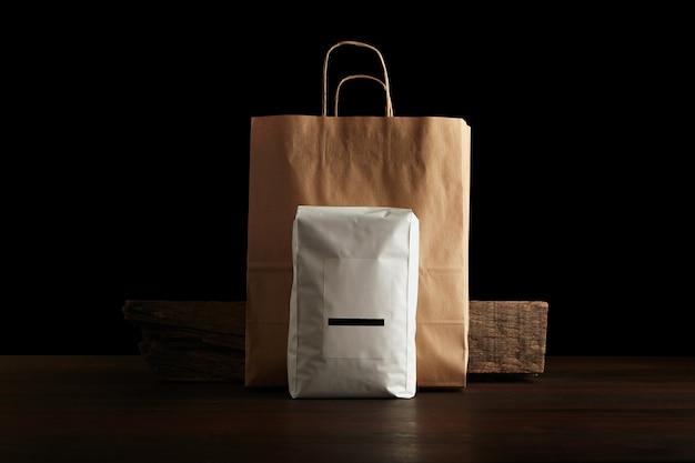 Retailer merchandise pack: groot hermetisch zakje wit met blanco label gepresenteerd voor ambachtelijke papieren zak en rustieke houten steen op rode tafel Gratis Foto