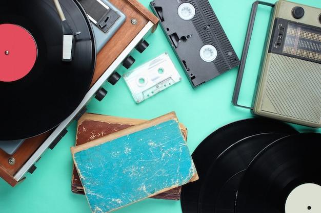 Retro attributen, 80s media. vinyl speler, videocassettes, audiocassettes, platen, radio, oude boeken op blauwe achtergrond. bovenaanzicht Premium Foto