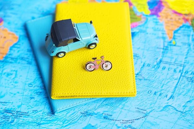 Retro auto en fiets op kleurrijke wereldkaart, paspoort Premium Foto