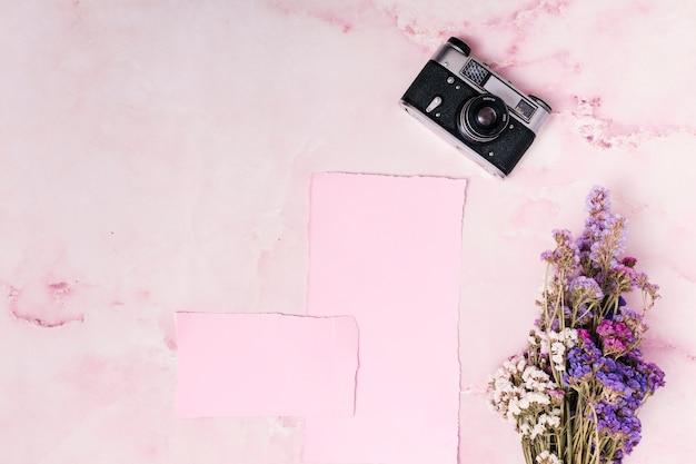 Retro camera in de buurt van papieren en bos bloemen Gratis Foto