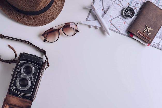 Retro camera met reismateriaal en punten op witte achtergrond met exemplaarruimte Premium Foto