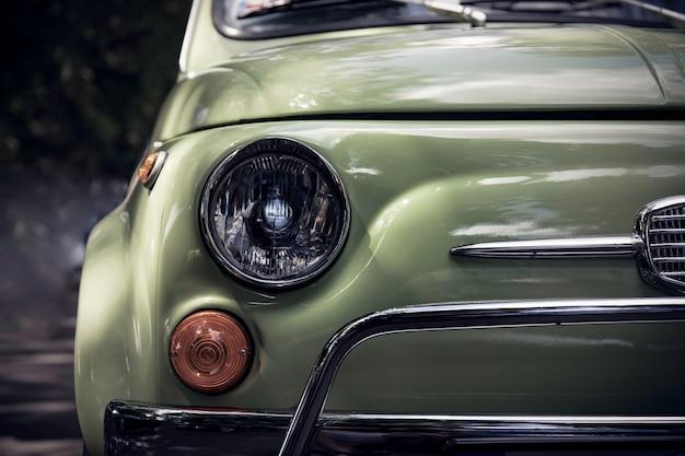Retro gestileerd beeld van een voorzijde van een groene klassieke auto. Premium Foto