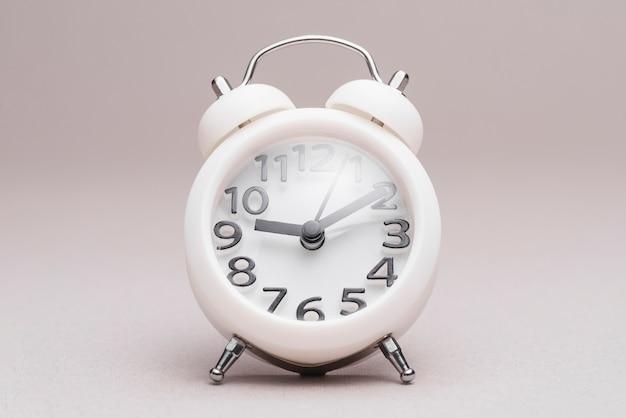 Retro gestileerde wekker op duidelijke achtergrond Gratis Foto