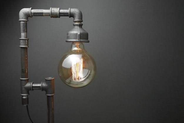 Retro lamp gemaakt van metalen waterleidingen met een edison lamp op een grijze achtergrond. het concept is een goed idee. Premium Foto