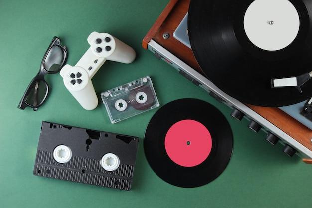 Retro media en entertainmentartikelen uit de jaren 80. vinylspeler, video, audiocassettes, 3d-bril, gamepad op groen oppervlak. Premium Foto