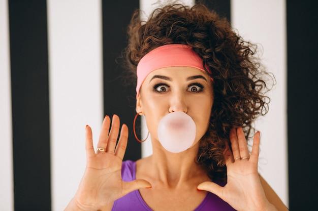 Retro meisjes blazende bel met kauwgom Gratis Foto