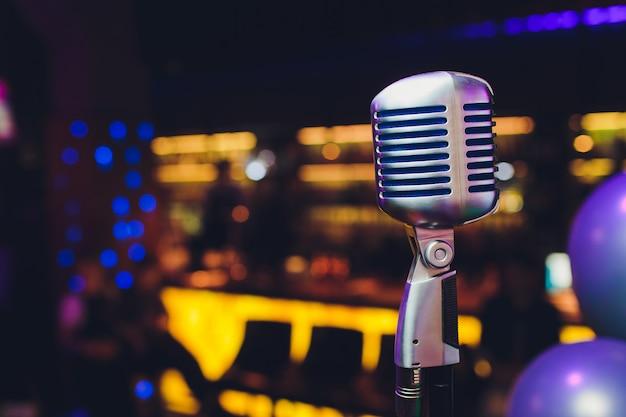Retro microfoon tegen onduidelijk beeld kleurrijk licht restaurant Premium Foto