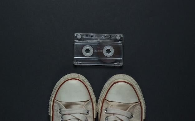 Retro oude sneakers en audiocassette op een zwarte achtergrond. jaren 80. bovenaanzicht Premium Foto