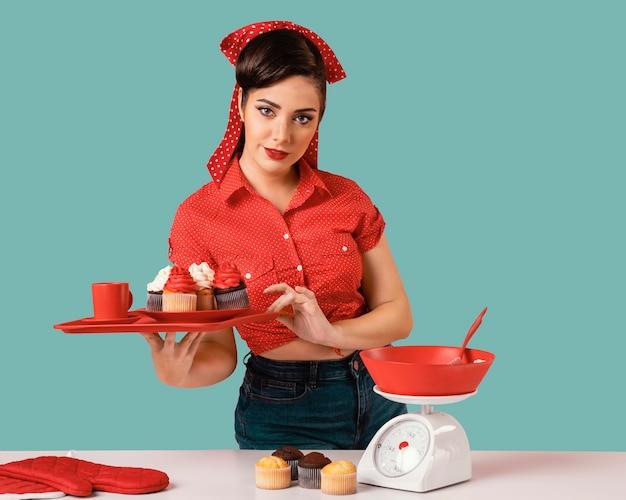 Retro pinup meisje poseren in een keuken Gratis Foto