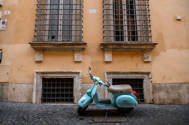Retro scooter geparkeerd in de smalle straten van rome Premium Foto