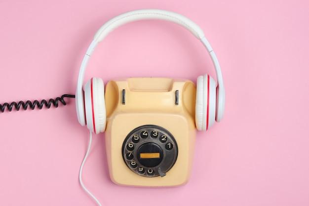 Retro-stijl creatieve plat leggen. roterende vintage telefoon met klassieke witte oortelefoons op roze achtergrond. pop cultuur. Premium Foto