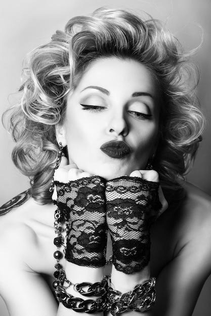 Retro stijl zwart-wit portret van sexy volwassen speelse vrouw die een kus blaast Premium Foto