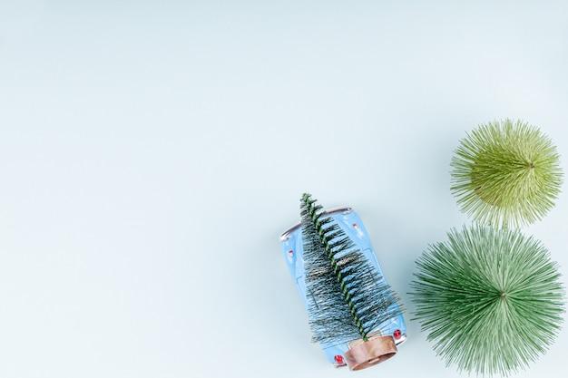 Retro stuk speelgoed auto carring sparren blauwe achtergrond, kerstmis het winkelen kaart Premium Foto