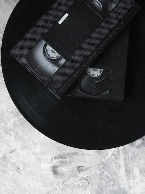 Retro vhs videocassettes uit de jaren 80 en vinylplaten op een grijze betonnen ondergrond. de oudste media. bovenaanzicht Premium Foto