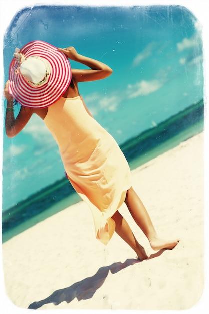 Retro vintage foto van hete mooie vrouw in kleurrijke sunhat en kleding die dichtbij strandoceaan lopen op hete de zomerdag op wit zand Gratis Foto