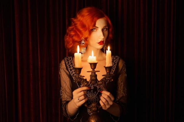 Retro vrouw met rode kinky haren in zwarte vintage jurk. vintage roodharige vrouw met rode lippen houdt kandelaar met brandende kaarsen. noir mode. kaarsen branden in kandelaar. noir portret. jaren 20 Premium Foto