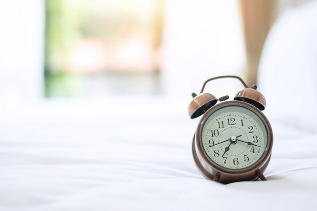Retro wekker op bed in de ochtendzon, wakker worden, vers ontspannen, een mooie dag en dagelijkse routine concept Premium Foto