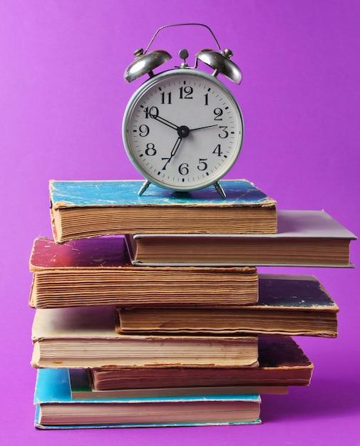 Retro wekker op stapel oude boeken op paarse tafel. Premium Foto