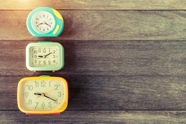 Retro wekkers op houten lijst. retro of vintage kleur gefilterd. oude tijd concept. Premium Foto
