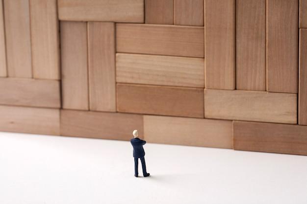 Reusachtige muur en miniatuurzakenman Premium Foto