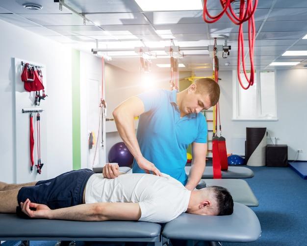 Revalidatietherapie. fysiotherapeut die met jonge mannelijke patiënt werkt Premium Foto
