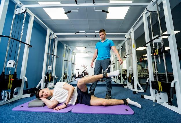 Revalidatietherapie. jonge man doen oefeningen op mat onder toezicht van fysiotherapeut. Premium Foto
