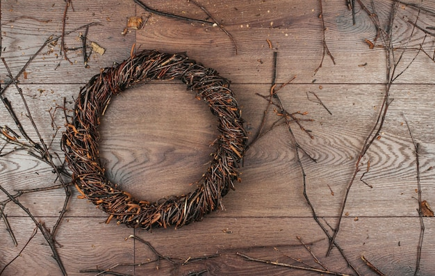 Rieten krans van berkentakken op een houten achtergrondexemplaarruimte. een krans van takken weven. Premium Foto