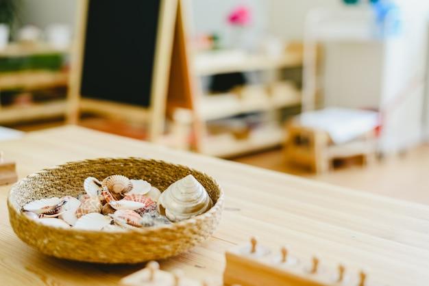 Rieten mand met zeeschelpen in een montessoriklasse Premium Foto