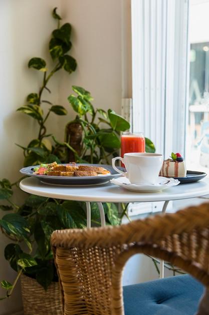 Rieten Ronde Tafel.Rieten Stoel Dichtbij De Witte Rondetafel Met Koffiekop Ontbijt