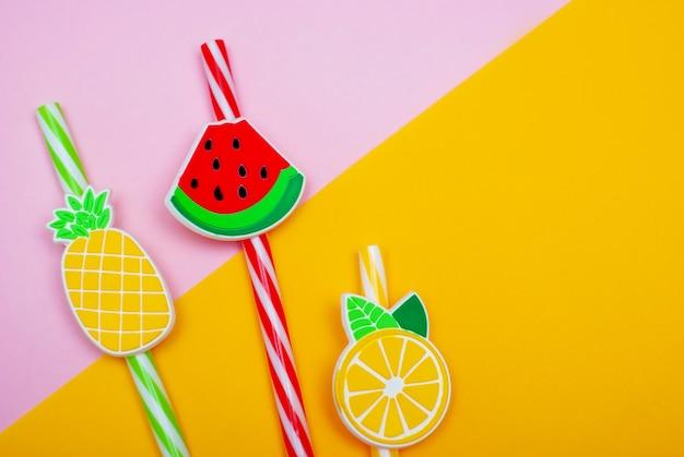 Rietjes in de vorm van watermeloen, citroen en ananas op een roze en gele achtergrond Premium Foto