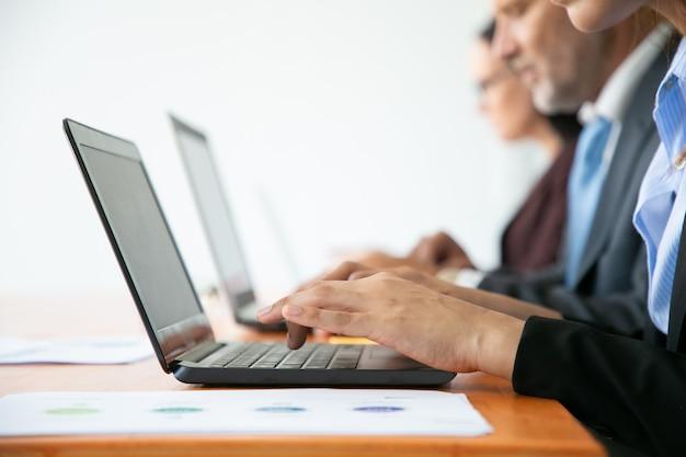 Rij van bedrijfsmensen die bij computers werken. handen van werknemers die op laptop toetsenborden typen. Gratis Foto