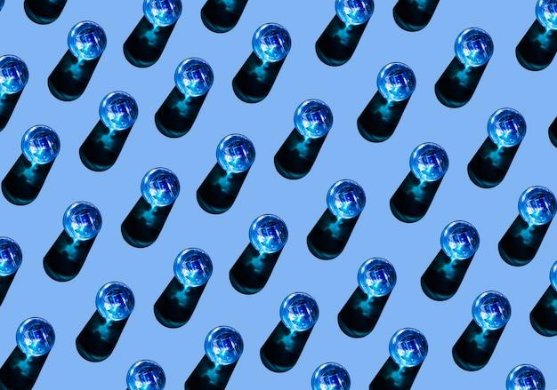 Rij van blauwe vloeibare glazen met schaduw op gekleurde achtergrond Gratis Foto
