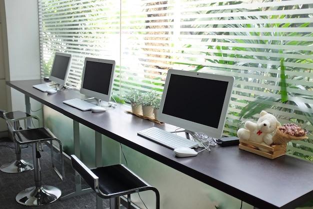 Rij van computers die op mensengebruik wachten bij internetcafé. Premium Foto