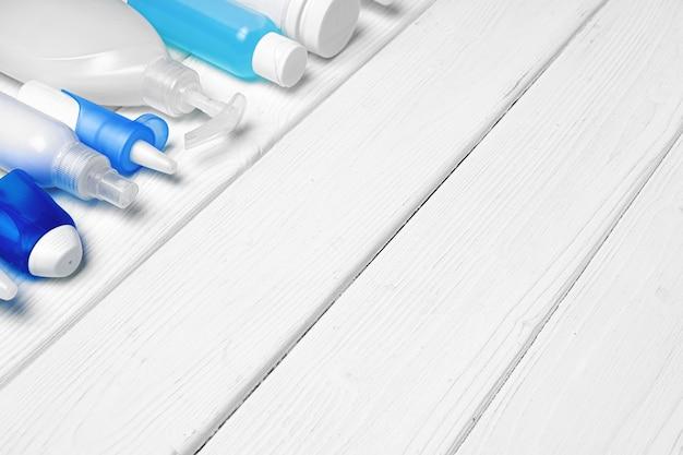 Rij van flessen met handdesinfecterende middelen, vloeibare zeep en medische preparaten op houten achtergrond Premium Foto