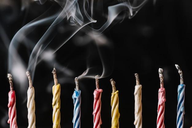 Rij van gedoofde kaarsen gerangschikt op zwarte achtergrond Gratis Foto