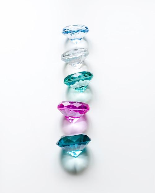 Rij van gekleurde diamanten met schaduw op witte achtergrond Gratis Foto