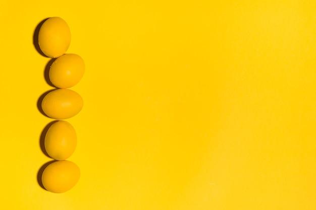 Rij van gele paaseieren op gele lijst Gratis Foto