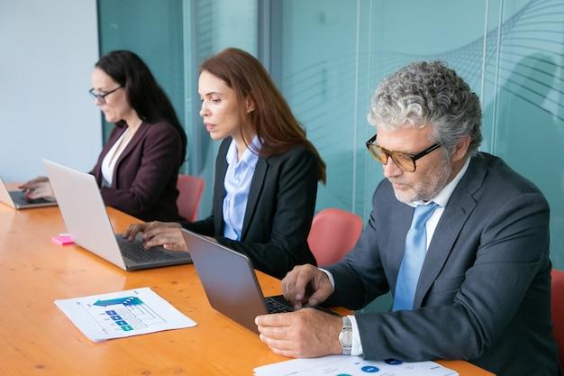 Rij van gerichte bedrijfsmensen die bij computers aan één tafel werken met papieren grafieken Gratis Foto