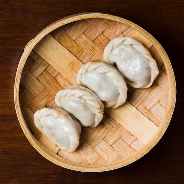 Rij van gestoomde dumplings dim sum in bamboestoomboot op lijst Gratis Foto