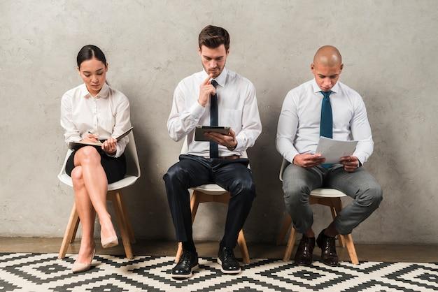 Rij van jonge mensen die door muur zitten terwijl het wachten op hun draai voor gesprek Gratis Foto