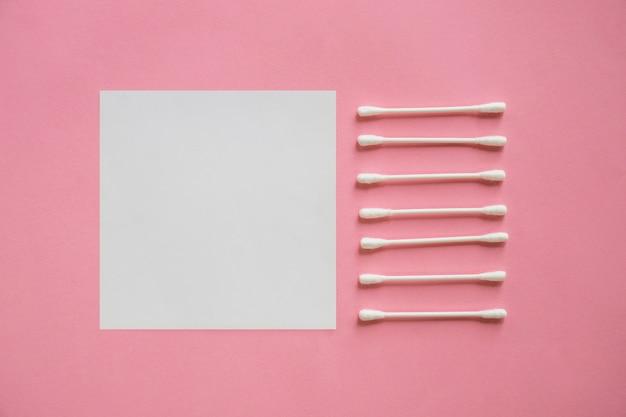 Rij van katoenen zwabbers dichtbij de lege zelfklevende nota over roze achtergrond Gratis Foto