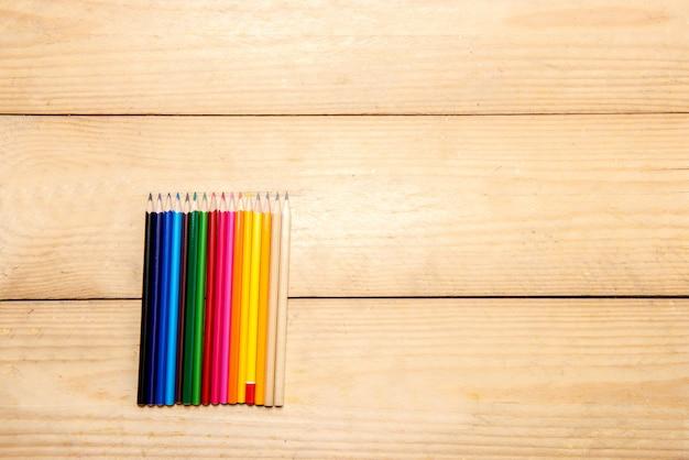 Rij van kleurrijke kantoorbehoeften van potloden voor het trekken op de houten lijst Premium Foto