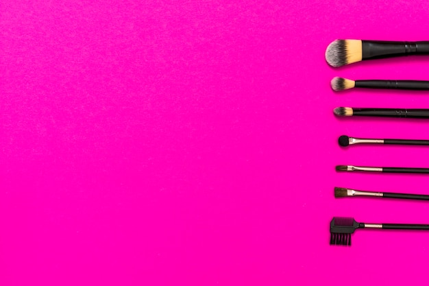 Rij van make-up borstels met kopie ruimte voor het schrijven van de tekst op roze achtergrond Gratis Foto