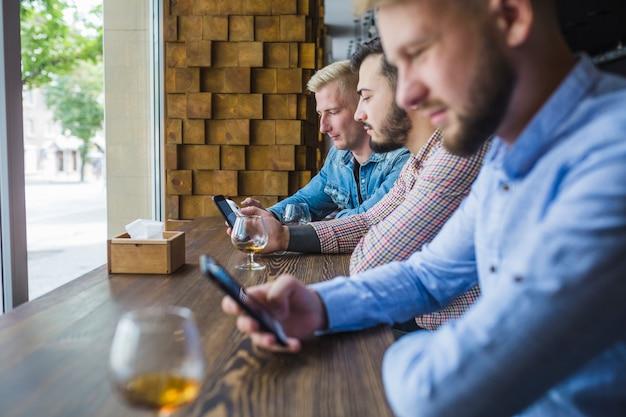 Rij van mannelijke vrienden met behulp van hun mobiele telefoons in het restaurant Gratis Foto