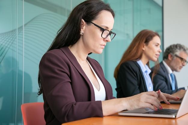 Rij van serieuze zakenmensen met behulp van laptops, zittend aan een tafel en typen Gratis Foto