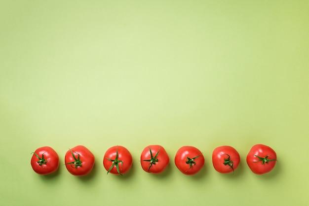 Rij van verse rode tomaten. minimaal ontwerp. vegetarisch, veganistisch, biologisch voedsel en alkalisch maaltijdconcept Premium Foto