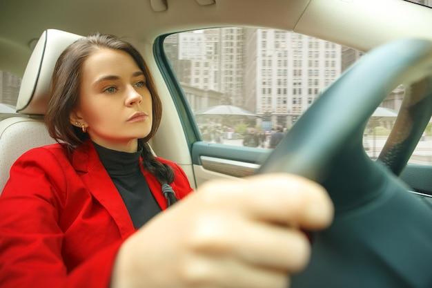 Rijden door de stad. jonge aantrekkelijke vrouw die een auto drijft. jong vrij kaukasisch model in elegante modieuze rode jas die bij modern voertuiginterieur zit. zakenvrouw concept. Gratis Foto