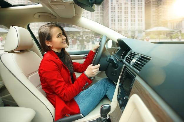 Rijden door de stad. jonge aantrekkelijke vrouw die een auto drijft. jong vrij kaukasisch model in elegante modieuze rode jas die bij modern voertuiginterieur zit Gratis Foto